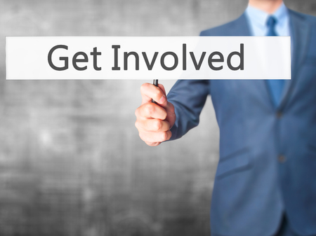 common goal: Get Involved - Businessman hand holding sign. Business, technology, internet concept. Stock Photo