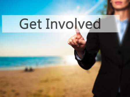 involved: Get Involved - Businesswoman hand pressing button on touch screen interface.