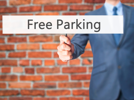hand holding sign: Free Parking - Businessman hand holding sign. Business, technology, internet concept. Stock Photo
