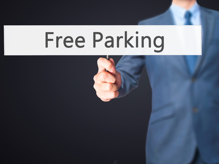 multi storey: Free Parking - Businessman hand holding sign. Business, technology, internet concept. Stock Photo