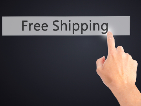 hand free: Free Shipping  - Hand pressing a button on blurred background concept . Business, technology, internet concept. Stock Photo