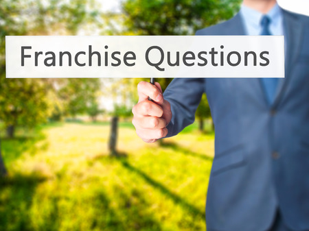 franchising: Franchise Questions - Businessman hand holding sign. Business, technology, internet concept. Stock Photo