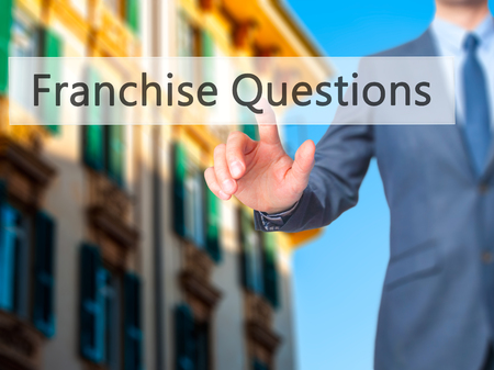 franchising: Franchise Questions - Businessman hand pressing button on touch screen interface. Business, technology, internet concept. Stock Photo