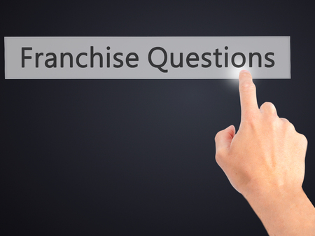 franchising: Franchise Questions - Hand pressing a button on blurred background concept . Business, technology, internet concept. Stock Photo