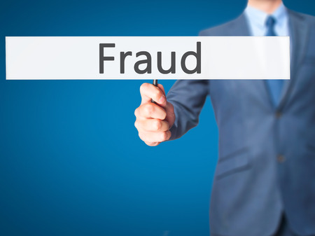 theft prevention: Fraud - Businessman hand holding sign. Business, technology, internet concept. Stock Photo Stock Photo