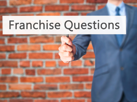 to incorporate: Franchise Questions - Businessman hand holding sign. Business, technology, internet concept. Stock Photo