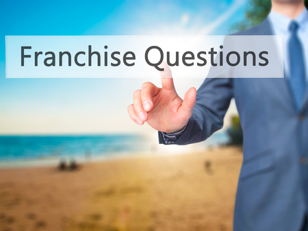 to incorporate: Franchise Questions - Businessman hand pressing button on touch screen interface. Business, technology, internet concept. Stock Photo