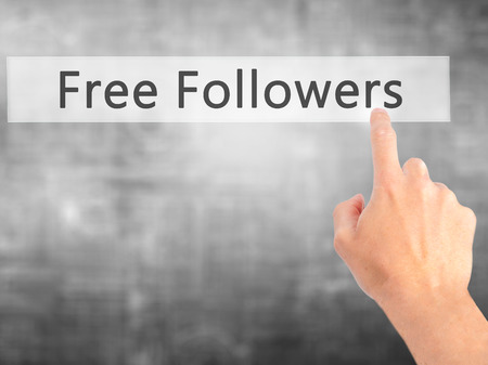 free me: Free Followers - Hand pressing a button on blurred background concept . Business, technology, internet concept. Stock Photo