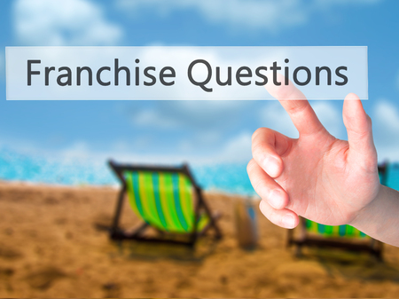 restaurant questions: Franchise Questions - Hand pressing a button on blurred background concept . Business, technology, internet concept. Stock Photo