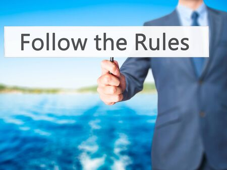comply: Follow the Rules - Businessman hand holding sign. Business, technology, internet concept. Stock Photo Stock Photo