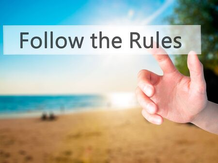 govern: Follow the Rules - Hand pressing a button on blurred background concept . Business, technology, internet concept. Stock Photo