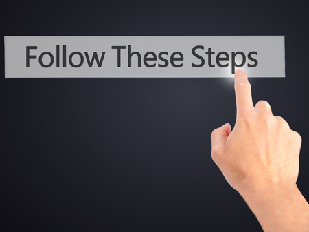 hand pointing: Follow These Steps - Hand pressing a button on blurred background concept . Business, technology, internet concept. Stock Photo Stock Photo