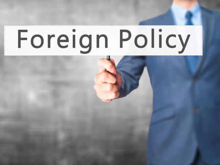 foreign nation: Foreign Policy - Businessman hand holding sign. Business, technology, internet concept. Stock Photo Stock Photo