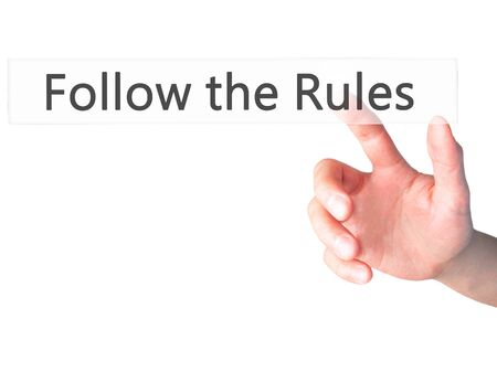 legality: Follow the Rules - Hand pressing a button on blurred background concept . Business, technology, internet concept. Stock Photo