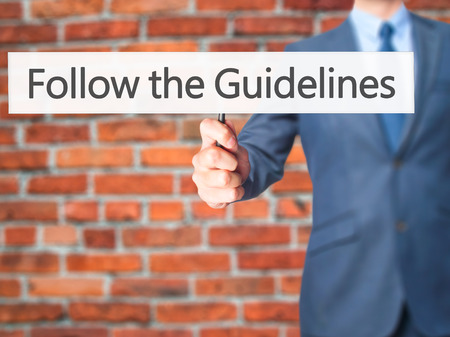 leeway: Follow the Guidelines - Businessman hand holding sign. Business, technology, internet concept. Stock Photo