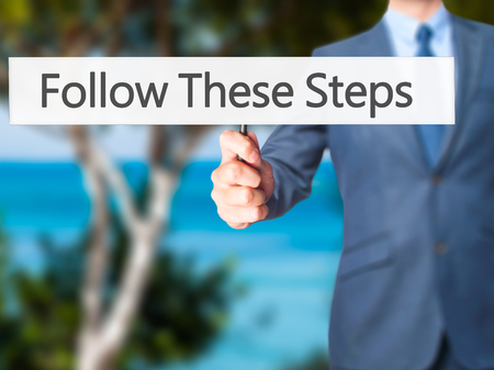 Follow These Steps - Businessman hand holding sign. Business, technology, internet concept. Stock Photo