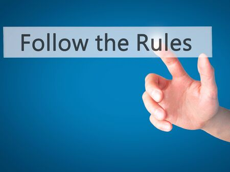 governing: Follow the Rules - Hand pressing a button on blurred background concept . Business, technology, internet concept. Stock Photo