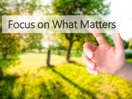 objectivism: Focus on What Matters - Hand pressing a button on blurred background concept . Business, technology, internet concept. Stock Photo Stock Photo