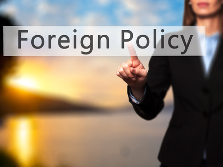 foreign nation: Foreign Policy - Businesswoman hand pressing button on touch screen interface. Business, technology, internet concept. Stock Photo