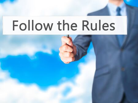 criteria: Follow the Rules - Businessman hand holding sign. Business, technology, internet concept. Stock Photo Stock Photo