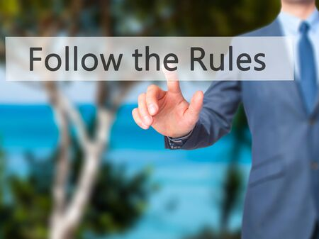 regulated: Follow the Rules - Businessman hand pressing button on touch screen interface. Business, technology, internet concept. Stock Photo