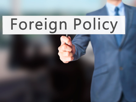 foreign national: Foreign Policy - Businessman hand holding sign. Business, technology, internet concept. Stock Photo Stock Photo