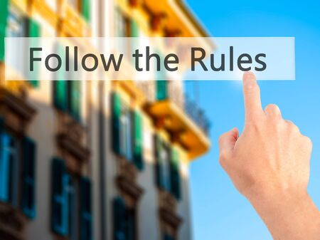 regulated: Follow the Rules - Hand pressing a button on blurred background concept . Business, technology, internet concept. Stock Photo