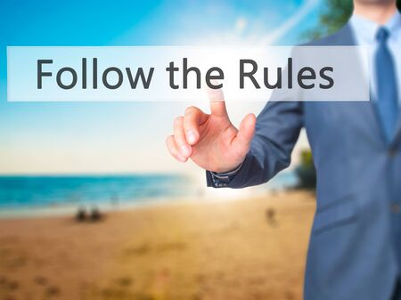 legality: Follow the Rules - Businessman hand pressing button on touch screen interface. Business, technology, internet concept. Stock Photo
