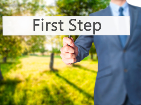 first step: First Step - Businessman hand holding sign. Business, technology, internet concept. Stock Photo