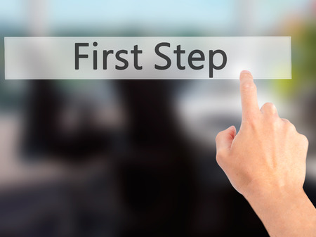 first step: First Step - Hand pressing a button on blurred background concept . Business, technology, internet concept. Stock Photo Stock Photo