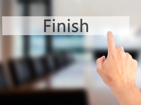 complete crossing: Finish - Hand pressing a button on blurred background concept . Business, technology, internet concept. Stock Photo