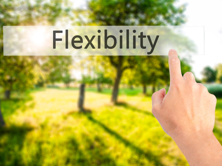 easygoing: Flexibility - Hand pressing a button on blurred background concept . Business, technology, internet concept. Stock Photo Stock Photo