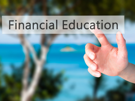 remuneraciones: Financial Education - Hand pressing a button on blurred background concept . Business, technology, internet concept. Stock Photo