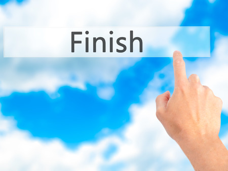 end of the trail: Finish - Hand pressing a button on blurred background concept . Business, technology, internet concept. Stock Photo