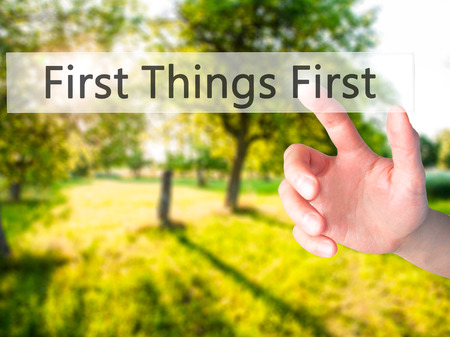 First Things First - Hand pressing a button on blurred background concept . Business, technology, internet concept. Stock Photo Stock fotó