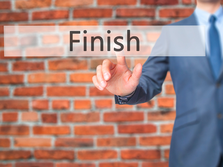 end of the trail: Finish - Businessman hand pressing button on touch screen interface. Business, technology, internet concept. Stock Photo Stock Photo