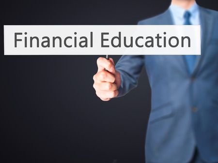 banco dinero: Financial Education - Businessman hand holding sign. Business, technology, internet concept. Stock Photo