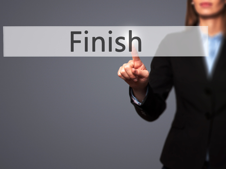 end of the trail: Finish - Businesswoman hand pressing button on touch screen interface. Business, technology, internet concept. Stock Photo