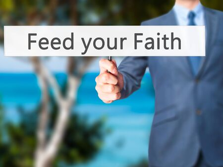 destiny: Feed your Faith - Businessman hand holding sign. Business, technology, internet concept. Stock Photo