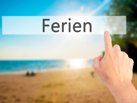 adjourned: Ferien (Vacation in German) - Hand pressing a button on blurred background concept . Business, technology, internet concept. Stock Photo Stock Photo