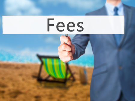 hidden taxes: Fees - Businessman hand holding sign. Business, technology, internet concept. Stock Photo Stock Photo