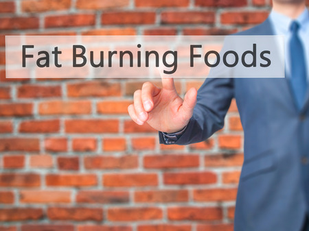 fat burning: Fat Burning Foods - Businessman hand pressing button on touch screen interface. Business, technology, internet concept. Stock Photo