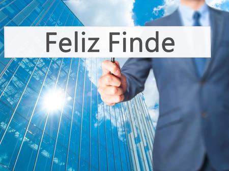 finde: Feliz Finde (Happy Weekend In Spanish)  - Businessman hand holding sign. Business, technology, internet concept. Stock Photo