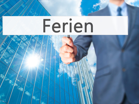 ferien: Ferien (Vacation in German) - Businessman hand holding sign. Business, technology, internet concept. Stock Photo