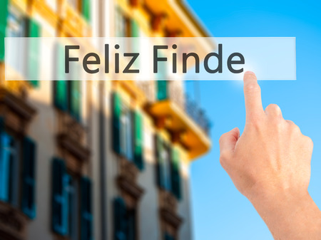 finde: Feliz Finde (Happy Weekend In Spanish)  - Hand pressing a button on blurred background concept . Business, technology, internet concept. Stock Photo