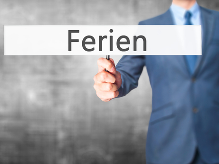 rescheduling: Ferien (Vacation in German) - Businessman hand holding sign. Business, technology, internet concept. Stock Photo