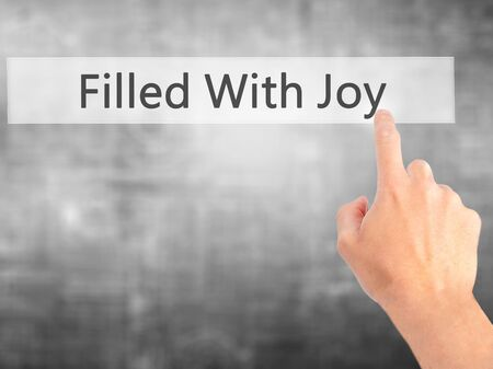 december 25th: Filled With Joy - Hand pressing a button on blurred background concept . Business, technology, internet concept. Stock Photo