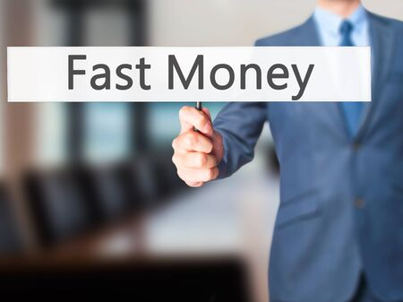adwords: Fast Money - Businessman hand holding sign. Business, technology, internet concept. Stock Photo