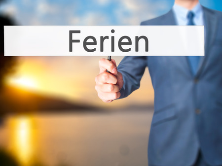 interruption: Ferien (Vacation in German) - Businessman hand holding sign. Business, technology, internet concept. Stock Photo