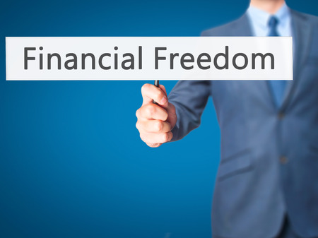 equities: Financial Freedom - Businessman hand holding sign. Business, technology, internet concept. Stock Photo
